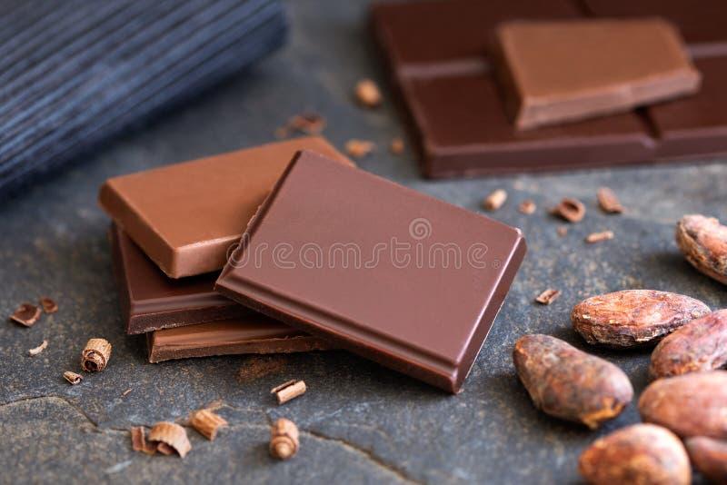 Fyra fyrkanter av mörker och mjölkar choklad med små chokladbitar på grå färger kritiserar bredvid kakaobönor Suddig choklad i royaltyfri fotografi