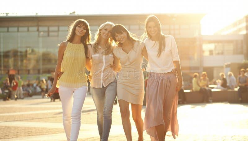 Fyra glade flickvänner på gå royaltyfria foton