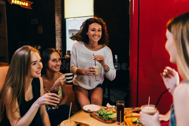 Fyra gladlynta flickvänner som har gyckel som pratar och skrattar att äta och att dricka i snabbmatrestaurang arkivbilder