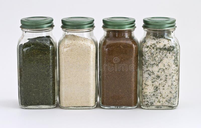 fyra glass jars inställda kryddor royaltyfri bild