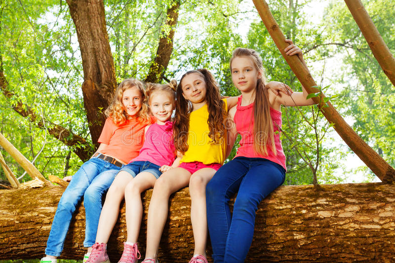 Fyra gulliga flickavänner som sitter på stupat träd arkivfoton