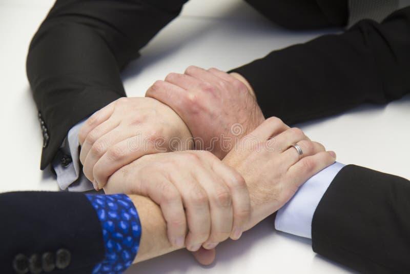Fyra händer som bildar en kedja royaltyfria bilder