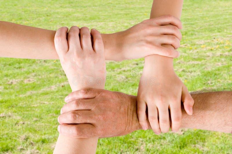 fyra händer som tillsammans sammanfogas royaltyfri fotografi