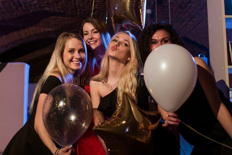 Fyra härliga unga Caucasian kvinnor som ut rymmer ballonger som har natt tillsammans i moderiktig stång royaltyfri bild
