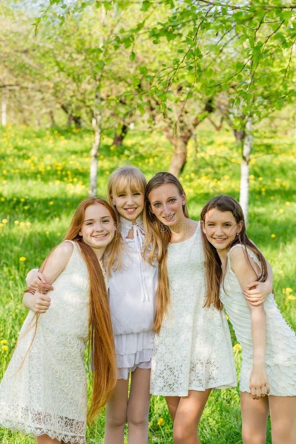 Fyra härliga unga flickor i vita klänningar i sommar royaltyfri fotografi