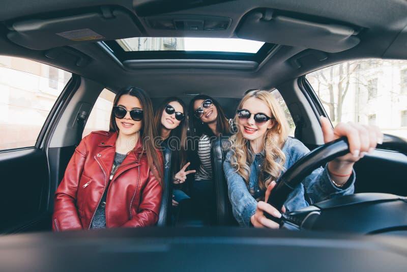 Fyra härliga unga gladlynta kvinnor som ser lyckliga och skämtsamma, medan sitta i bil royaltyfri bild