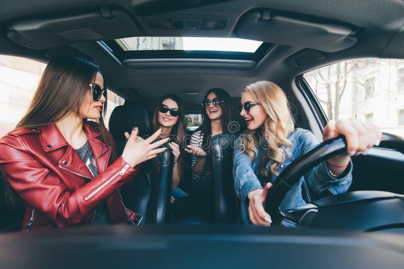 Fyra härliga unga gladlynta kvinnor som ser lyckliga och skämtsamma, medan sitta i bil arkivfoton