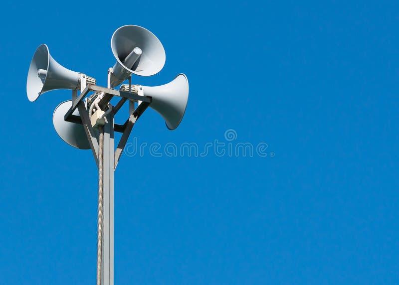 Fyra högtalare som fästas till en kugge på en blå bakgrund royaltyfria foton