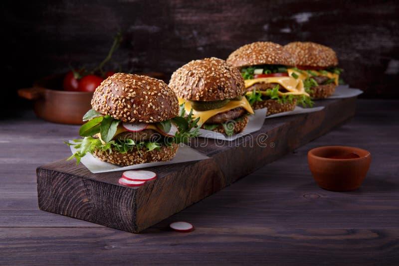 Fyra hemlagade hamburgare på trätabellen arkivfoto