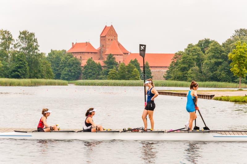 Fyra idrottsman nenflickor i coxed eka fyra på Galve sjön med den Trakai slotten på bakgrund Coxed fyra är en eka som in används fotografering för bildbyråer