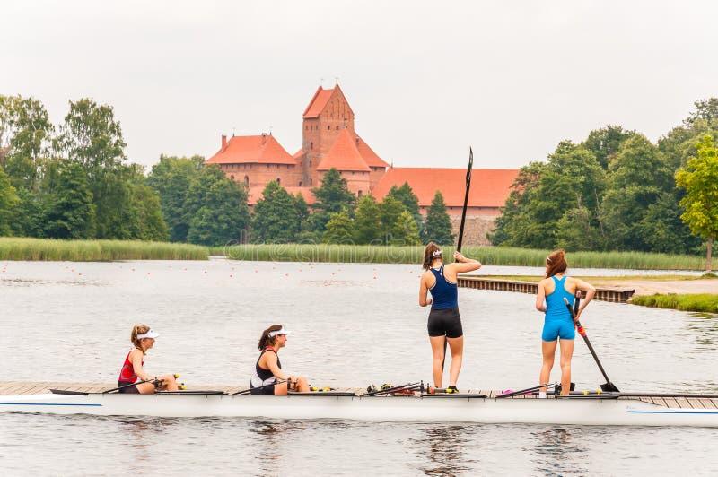 Fyra idrottsman nenflickor i coxed eka fyra på Galve sjön med den Trakai slotten på bakgrund Coxed fyra är en eka som in används royaltyfria bilder
