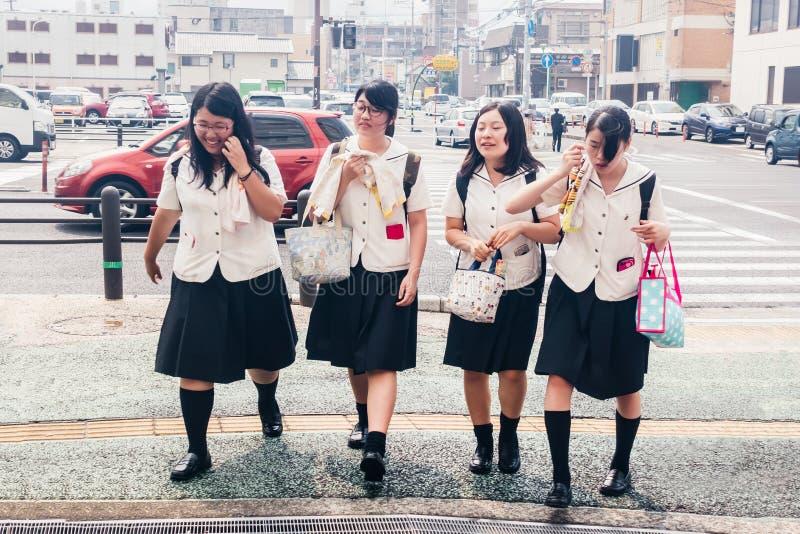 Fyra japanska skolflickor som korsar gatan Värme i staden arkivfoton