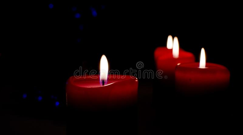 Fyra julljus på den svarta bakgrunden med blå bokeh arkivbilder