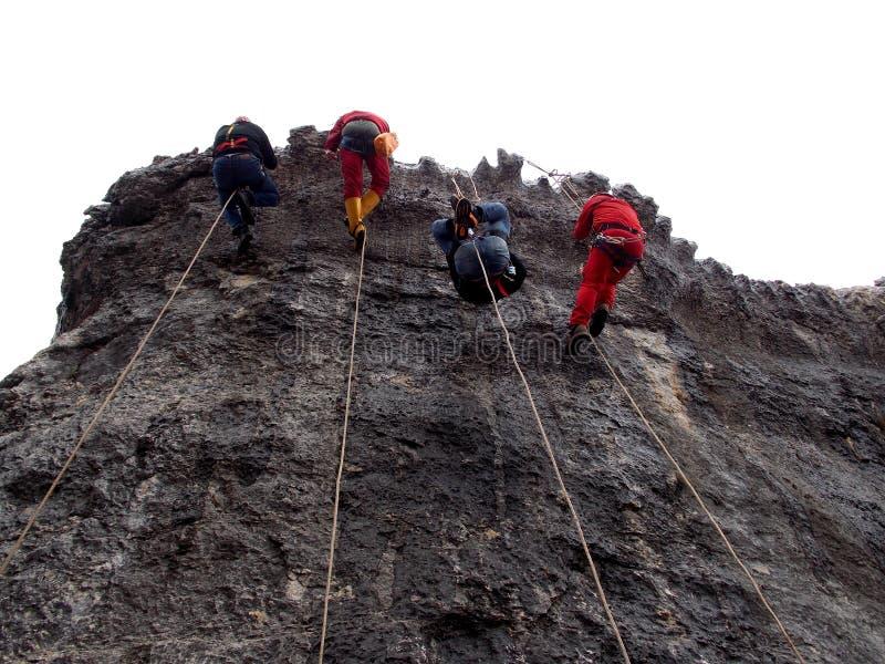 Fyra klättrare som rappelling genom att använda den enkla reptekniken arkivfoto