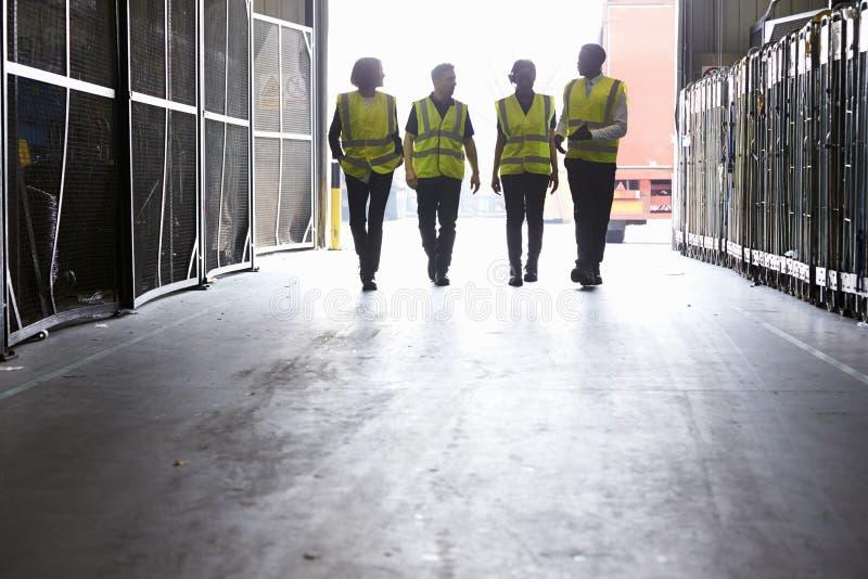 Fyra kollegor i reflekterande västar som går in i ett lager arkivbilder