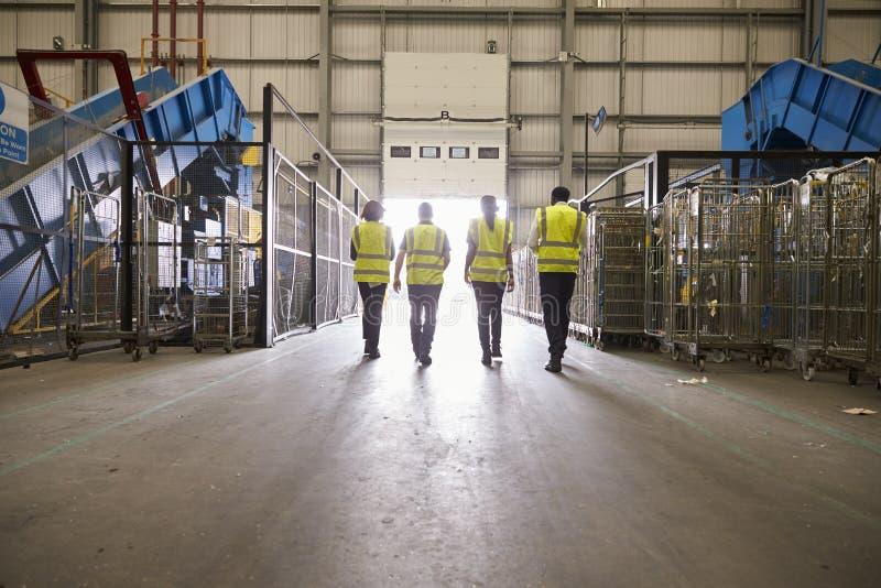 Fyra kollegor i reflekterande västar som lämnar ett lager royaltyfri bild