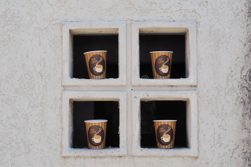 Fyra kopp kaffe i fönstret royaltyfria foton
