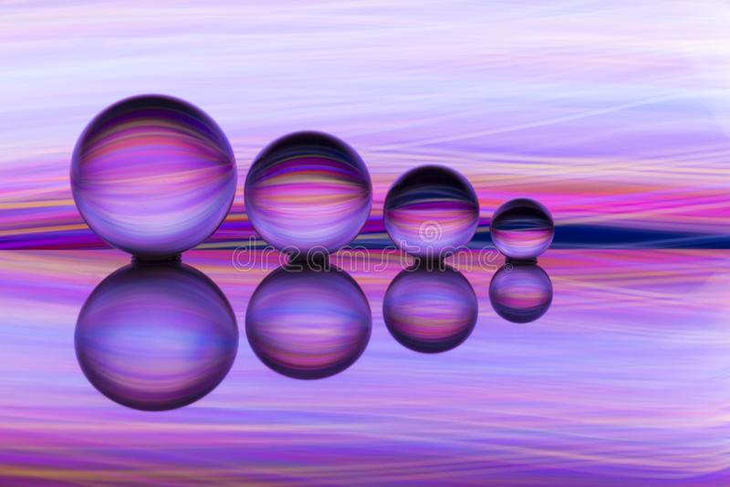 Fyra kristallkulor i rad med färgrika strimmor av regnbågefärg bak dem arkivfoto