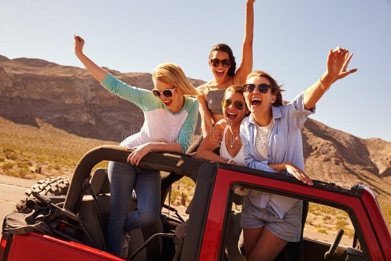 Fyra kvinnliga vänner på anseende för vägtur i konvertibel bil arkivbild