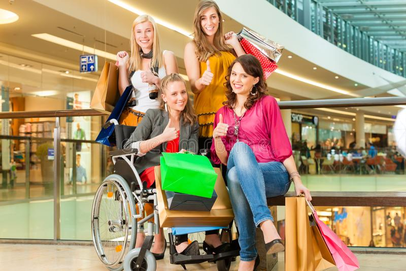 Fyra kvinnliga vänner som shoppar i en galleria med rullstolen arkivfoton