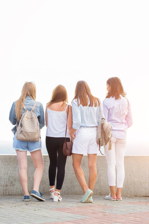 Fyra kvinnor står tillbaka för att dra tillbaka och diskutera något i natur arkivbilder