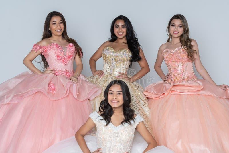 Fyra latinamerikanska flickor i Quinceanera klänningar royaltyfri bild