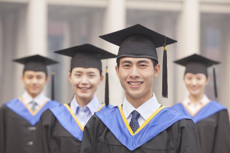 Fyra le universitetkandidater i avläggande av examenkappor och akademikermössor som ser kameran royaltyfri bild