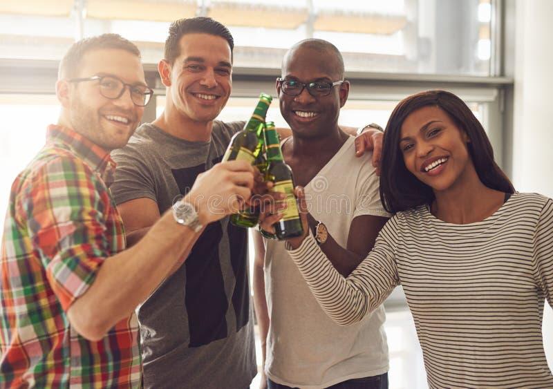 Fyra le vänner som knackar lätt på ölflaskor arkivfoto