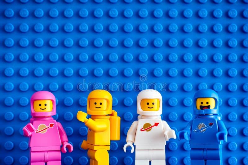 Fyra Lego astronautminifigures mot blå baseplatebakgrund arkivbilder