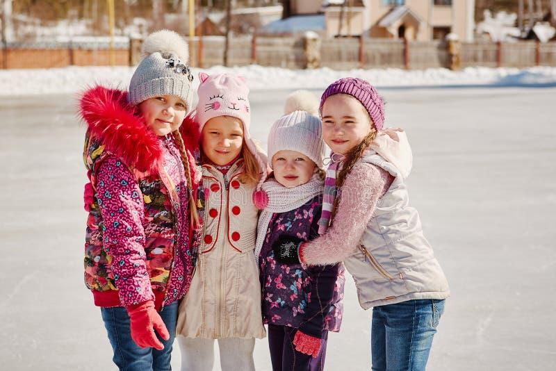 Fyra lilla lyckliga flickor åker skridskor De har gyckel med vänner royaltyfri fotografi