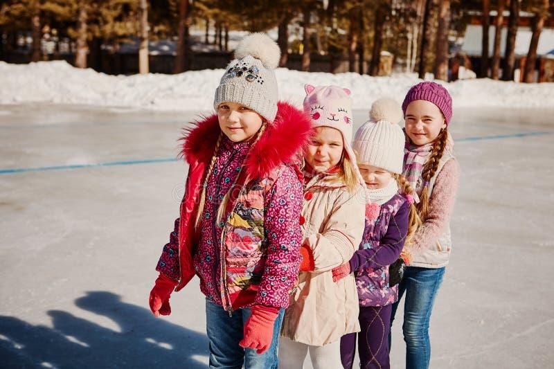Fyra lilla lyckliga flickor åker skridskor De har gyckel med vänner arkivbilder