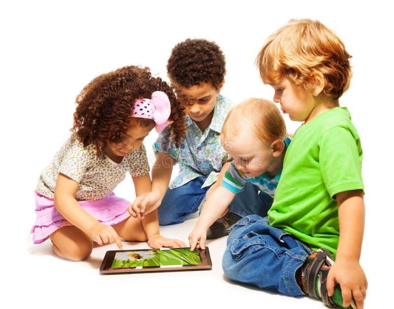 Fyra lite ungar som leker tableten fotografering för bildbyråer