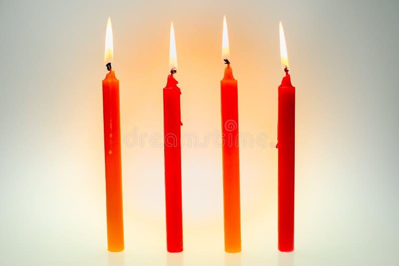 Fyra ljusa flammastearinljus som ljust bränner arkivfoto