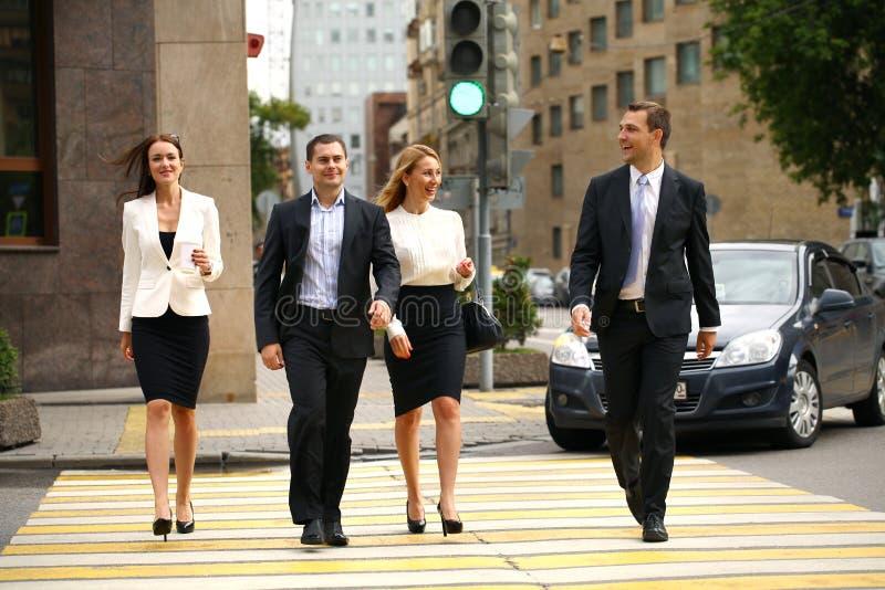 Fyra lyckade affärspersoner som korsar gatan i staden arkivfoto