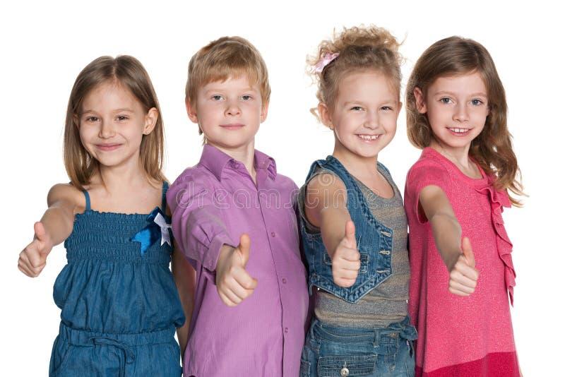 Fyra lyckliga barn rymmer upp hans tummar fotografering för bildbyråer