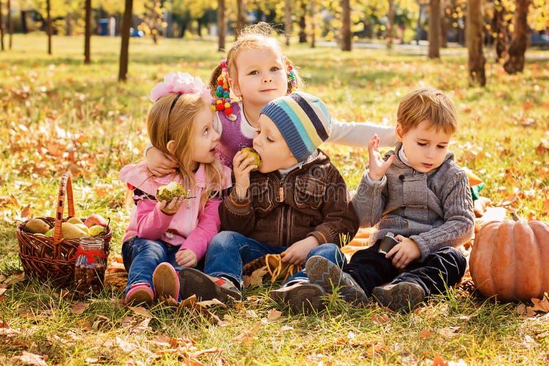 Fyra lyckliga barn som in spelar, parkerar med frukter royaltyfri foto