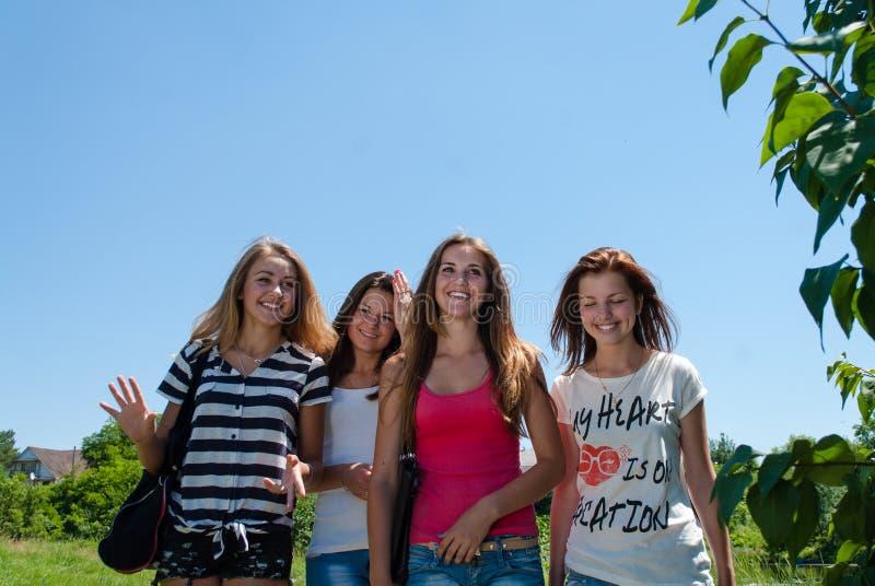 Fyra lyckliga flickavänner för unga kvinnor som tillsammans går mot blå himmel fotografering för bildbyråer