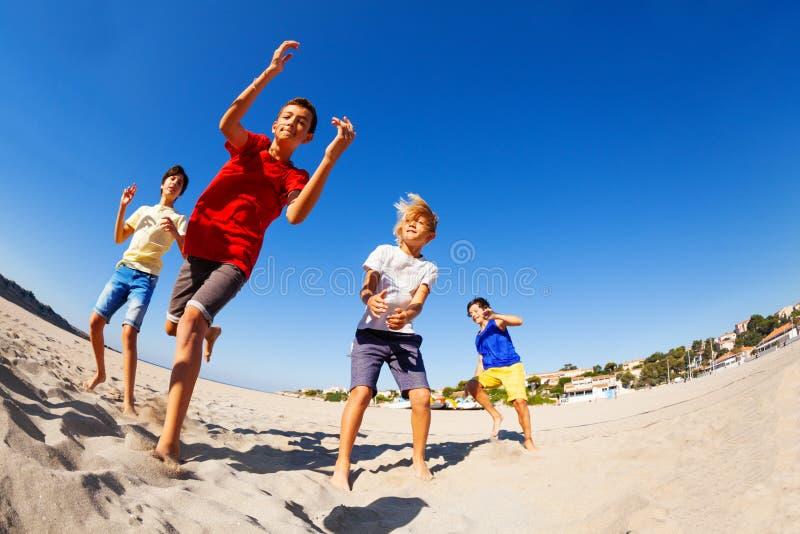 Fyra lyckliga pojkar som dansar på stranden i sommar arkivbild