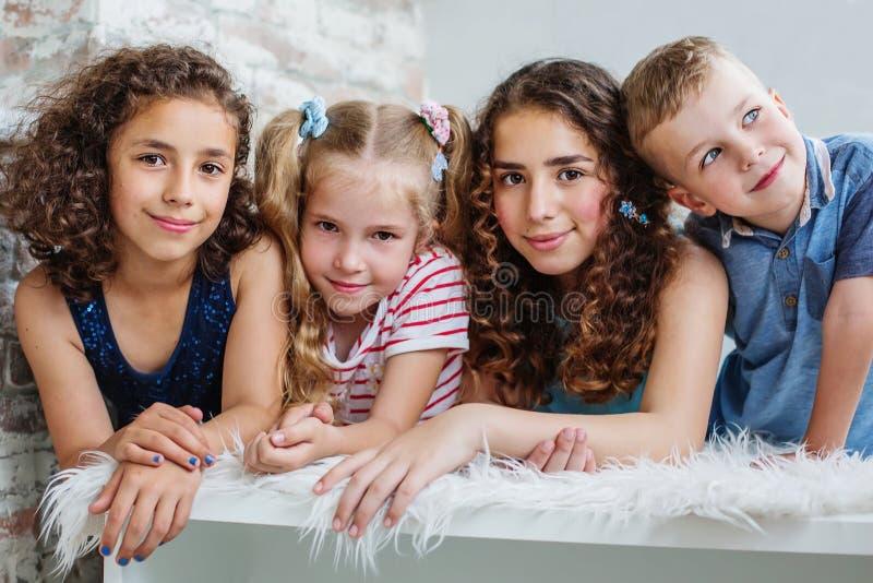 Fyra lyckliga småbarn i en omfamning royaltyfria foton