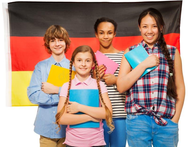 Fyra lyckliga studenter som står mot tysk flagga royaltyfria bilder