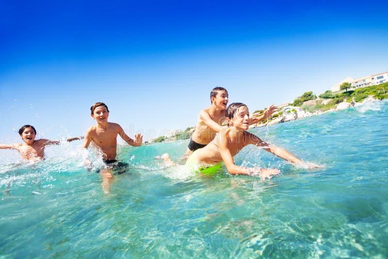 Fyra lyckliga tonårs- pojkar som simmar i havet royaltyfri fotografi