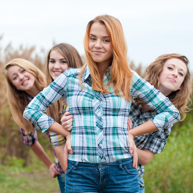 Fyra lyckliga tonårs- vänner arkivfoto