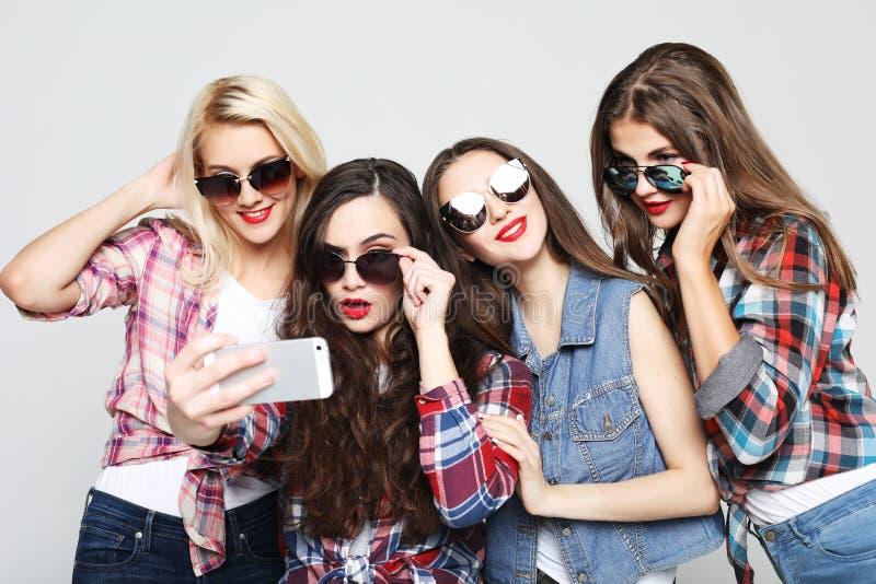 fyra lyckliga ton?rs- flickor med smartphonen som tar selfie royaltyfri foto