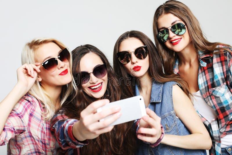 fyra lyckliga ton?rs- flickor med smartphonen som tar selfie royaltyfri fotografi