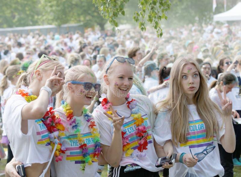 Fyra lyckliga unga flickor för starten i färgkörningen arkivbild