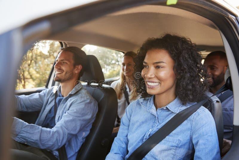 Fyra lyckliga unga vuxna vänner i en bil på en vägtur arkivfoton