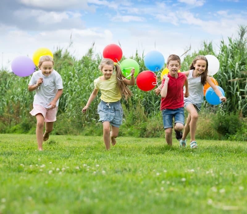 Fyra lyckliga ungar som kör på grön gräsmatta arkivfoto
