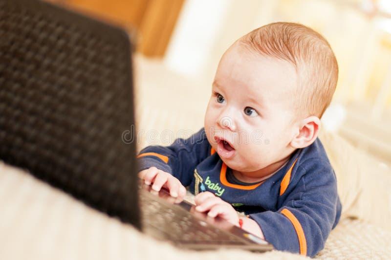 Fyra månader behandla som ett barn med bärbara datorn royaltyfria foton