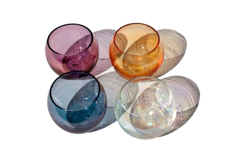 Fyra mångfärgade tappningrundaexponeringsglas på en vit bakgrund med härliga kulöra skuggor i solljus isolerat slut upp fotografering för bildbyråer