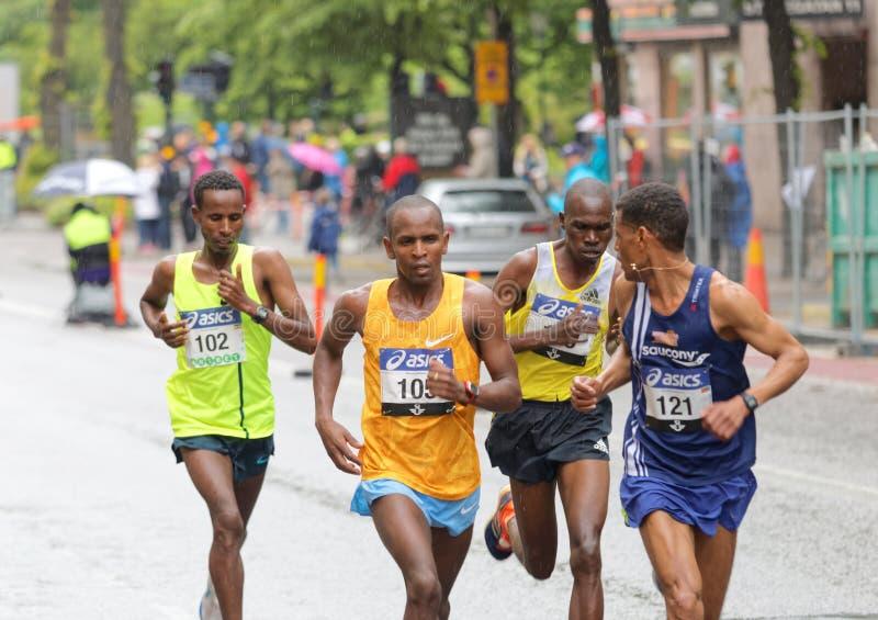 Fyra manliga löpare i täten royaltyfri bild